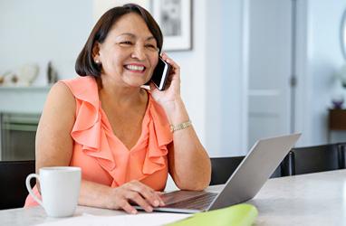 Persona hablando por teléfono mientras está en la computadora