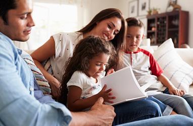 Familia leyendo en el sofá