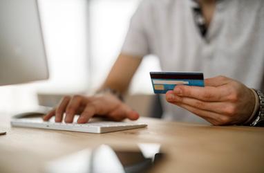 Persona en la computadora con una tarjeta bancaria