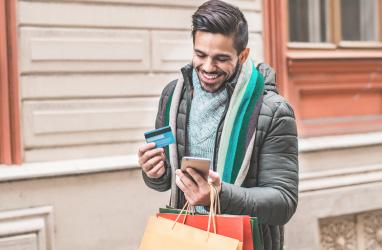 Persona caminando por la calle con un teléfono, una tarjeta bancaria y bolsas de la compra