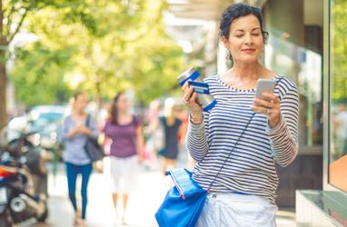 Persona caminando por la calle con un teléfono y una tarjeta bancaria